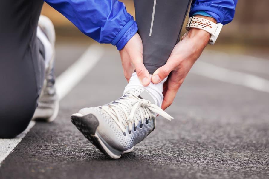 Runner Holds Injured Ankle