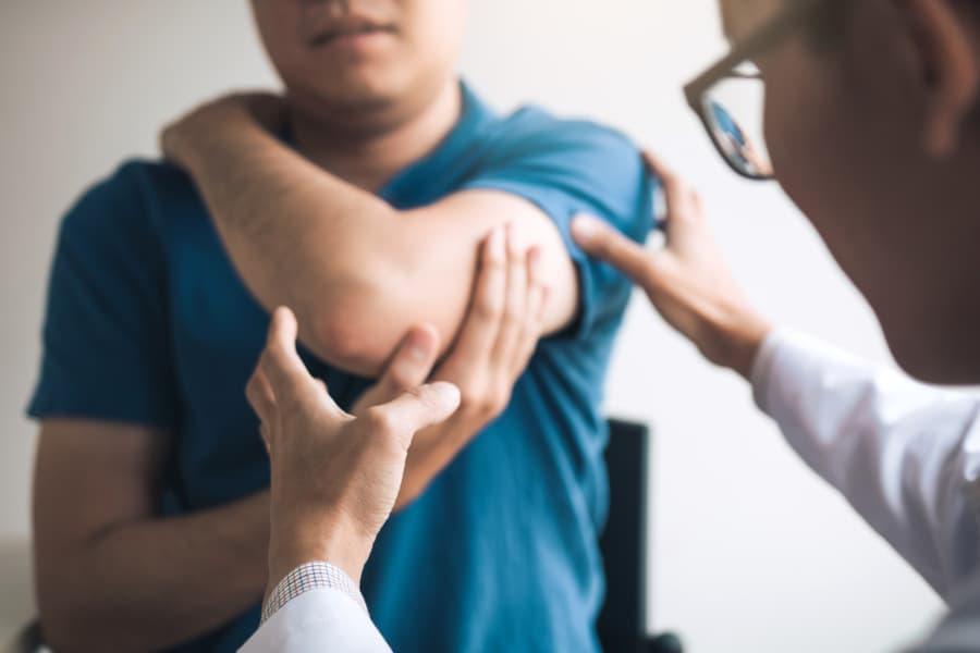 Doctor examines patient elbow