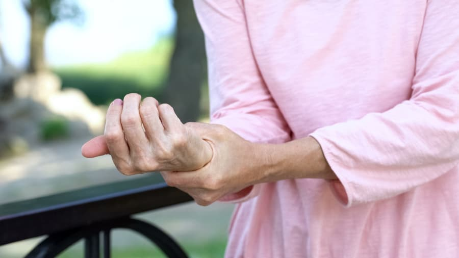Old Woman Holding Wrist